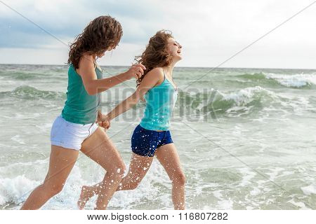 outdoor portrait of two young happy girls running on tropical sea background, holiday image
