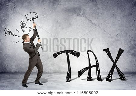 Businessman with hammer and word tax
