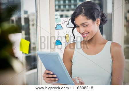 Smiling businesswoman using digital tablet against adhesive notes on window