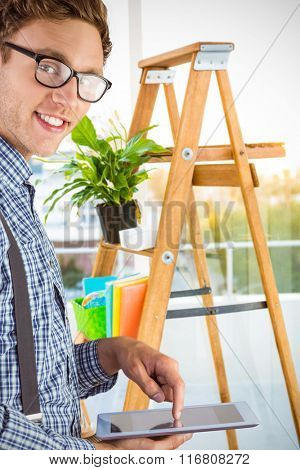 Geeky businessman using his tablet pc against ladder used as shelf in office