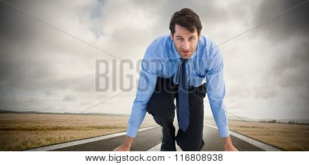 Focused businessman ready to race against road landscape