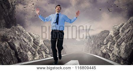 Happy businessman running with hands up against dark road landscape