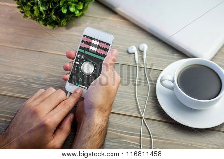 Music app against person using smart next to coffee mug at desk