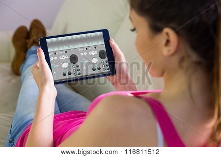 Woman using tablet at home against music app