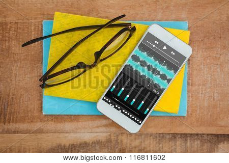 Music app against close up view of smartphone and glasses