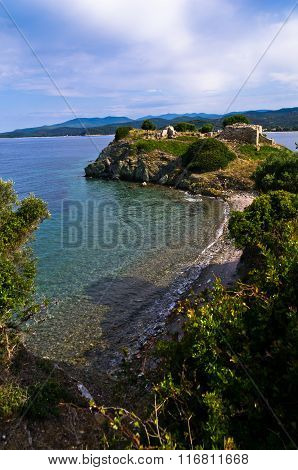 Beach with ruins of old roman fortress in background, Sithonia, Greece