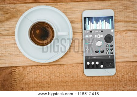 Music app against above view of a coffee and a smartphone