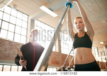 Young Woman Exercising With A Barbell In The Gym