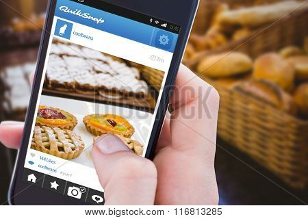 Woman using her mobile phone against close up of basket with fresh bread and pastry Close up of basket with fresh bread and pastry at the bakery
