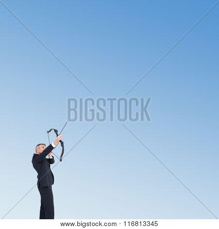 Businessman shooting bow and arrow against blue sky