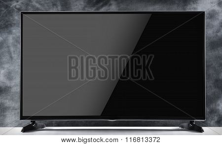 Flat tv on a dark background.