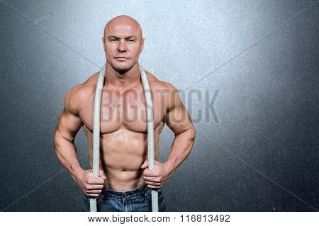 Portrait of healthy man holding rope against grey