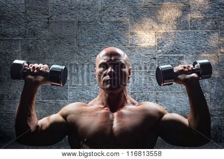 Portrait of man exercising with dumbbells against grey