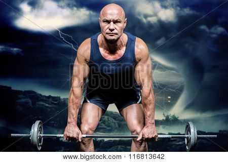 Portrait of muscular man exercising with crossfit against stormy sky with tornado over landscape