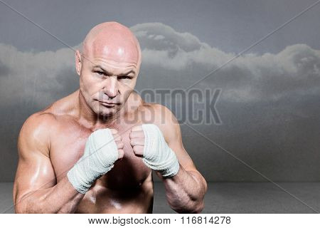 Portrait of confident man with fighting stance against clouds in a room