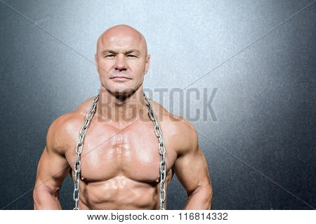 Portrait of fighter holding chain against grey
