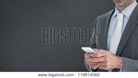 Portrait of confident businessman text messaginh through smart phone against grey background