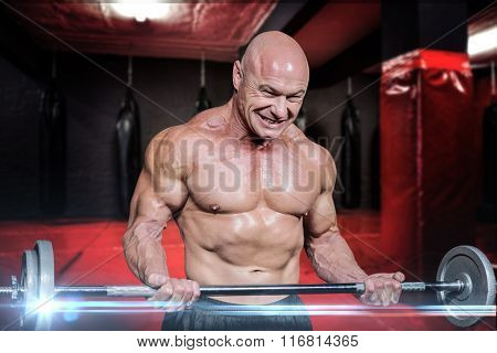 Passionate healthy man exercising while lifting crossfit against red boxing area with punching bags