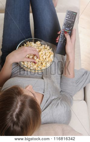 Young Woman Spending A Relaxing Weekend At Home Watching Tv