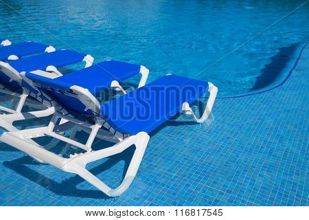 Deck Chairs Near The Swimming Pool