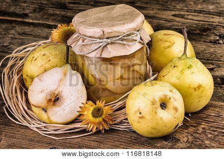 Ripe pears and a jar of pears compote rustic background