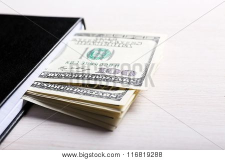 Dollars In Notebook On Light Wooden Background