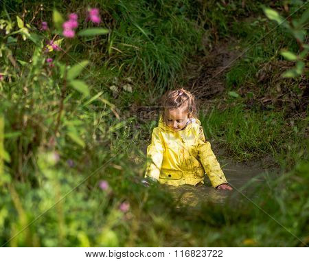 Young girl playing in deep puddle