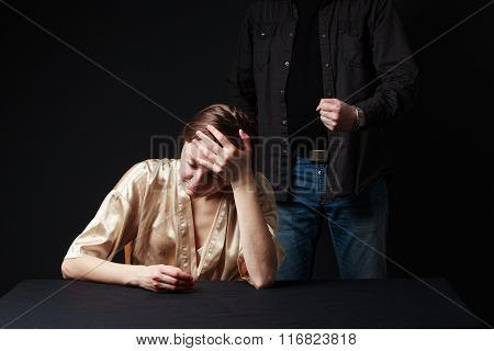 Sad Woman Is Sitting , Keeping Hand On The Forehead, Man's Figure  Behind