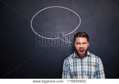 Portrait of angry young man with beard standing and shouting over blackboard background with drawn empty speech bubble