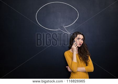 Thoughtful pretty young female talking on mobile phone over blackboard background with empty speech bubble