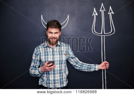 Bearded young man using smartphone standing over blackboard background with drawn horns and trident