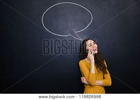 Smiling young woman talking on mobile phone over chalkboard background with drawn blank speech bubble