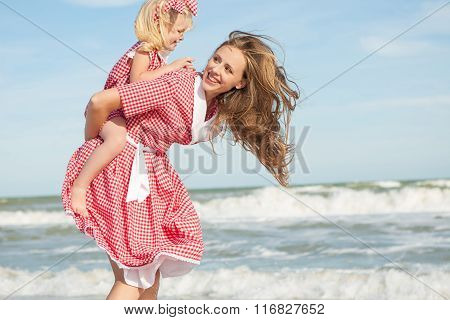 Mother And Her Daughter  Having Fun Playing On The Beach