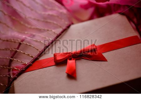 Vintage brown love box with red bow and pink background