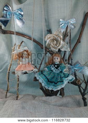 Porcelain dolls on swings photo