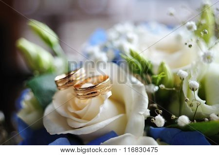 Two Gold Wedding Rings Lie On A White Rose