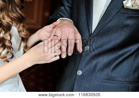 Bride Puts Wedding Ring On Groom Finger On Day Of The Wedding Ceremony