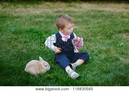 Little Boy In Suit With A Bouquet And A Rabbit