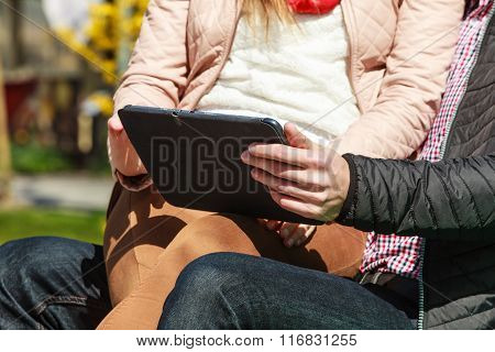 Couple With Tablet Sitting On Bench Outdoor