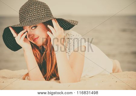 Beautiful redhaired happy girl in black hat on beach.