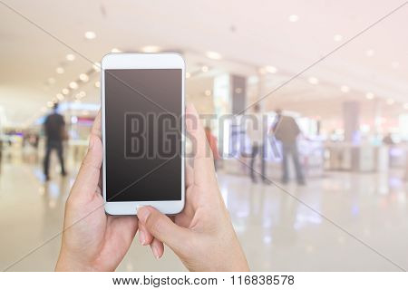Woman's And Holding Smart Phone With Blur Shopping Mall Background.