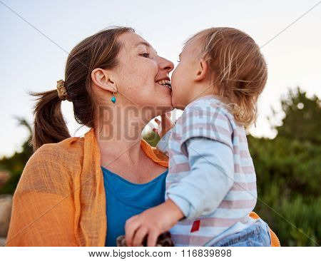 Mother plays with her little baby child outdoors