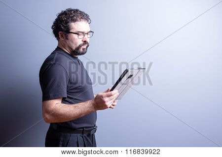 Man With Beard And Glasses Reading From Tablet