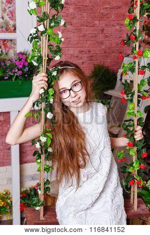 Teen Girl Sitting On A Swing.
