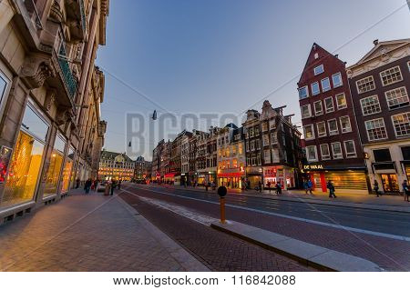 Amsterdam, Netherlands - July 10, 2015: Typical Dutch charming street with red brick houses on both
