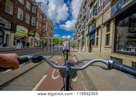 Amsterdam, Netherlands - July 10, 2015: Bikers point of view as bicycling through city streets