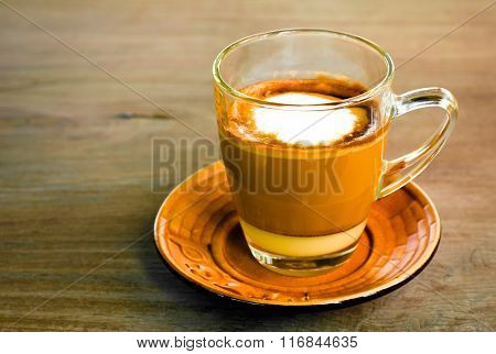 A Cup Of Hot Caramel Cappuccino Coffee In A Transparent Cup On Wooden Background