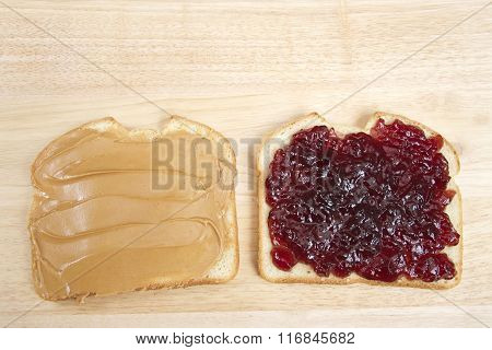 Peanutbutter And Jelly Sandwich On White Bread Open Face On Wood Table
