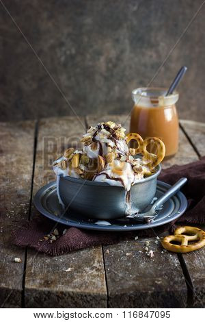Delicious Homemade  Ice Cream With Salted Caramel And Chocolate Sauce And Nuts In  Vintage Metal Bow