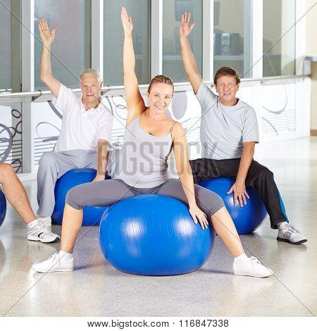 Happy senior group doing back training exercises in gym